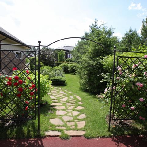 Вход в сад через металлическую арку с плетистыми розами