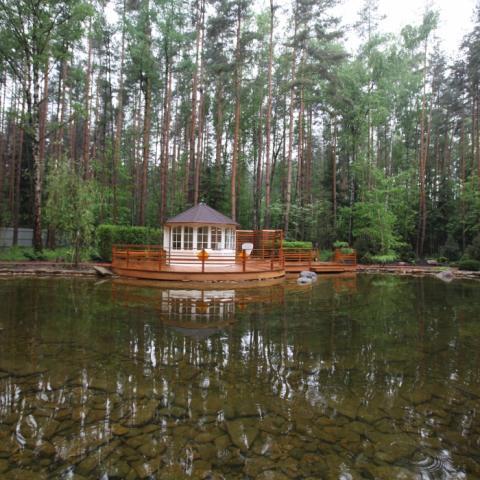 Готовый узел деревянного патио и беседки у пруда.