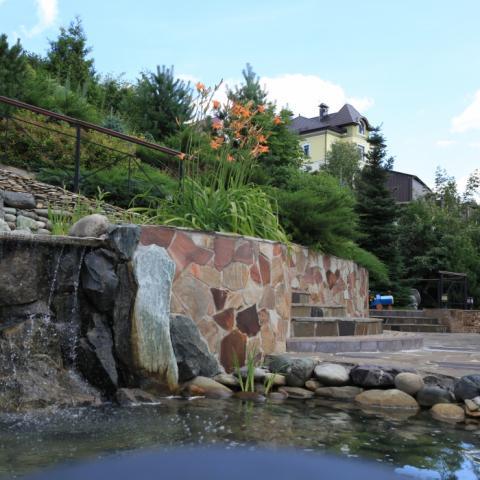 Водный каскад, прудик и патио на участке с большим перепадом высот
