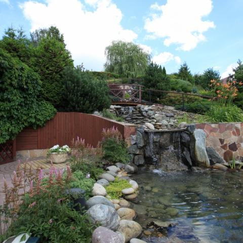 Водный каскад и прудик на участке с большим перепадом высот, подпорная стена облицованная лиственницей