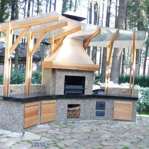 Уличныое барбекю, мангал, печь под навесом облицовано гранитом