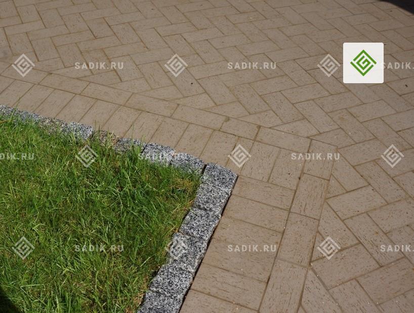 Бордюр отделяет газон от садовой дорожки, вымощенной плиткой