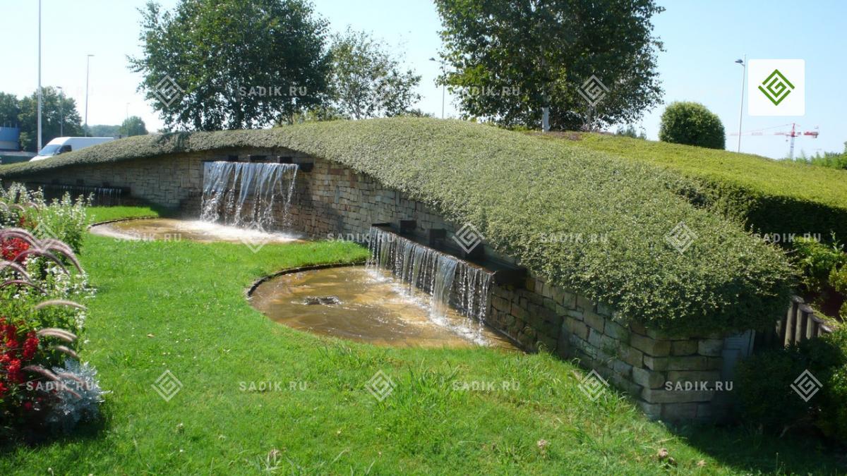 Фонтан в форме водопада у газона в европейском парке